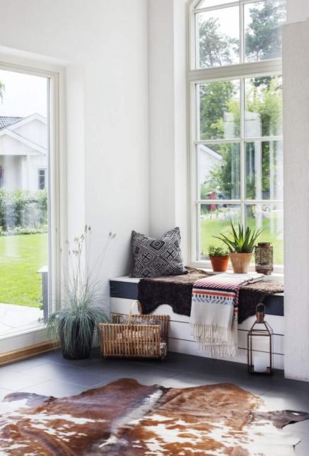 skandynawskie pledy,etniczne wzory w skandynawskich kocach,wiklinowy gazetnik,drewniany lampion,rustykalne dodatki we wnętrzach,siedzisko na oknie w skandynawskim domu,białe ściany w salonie