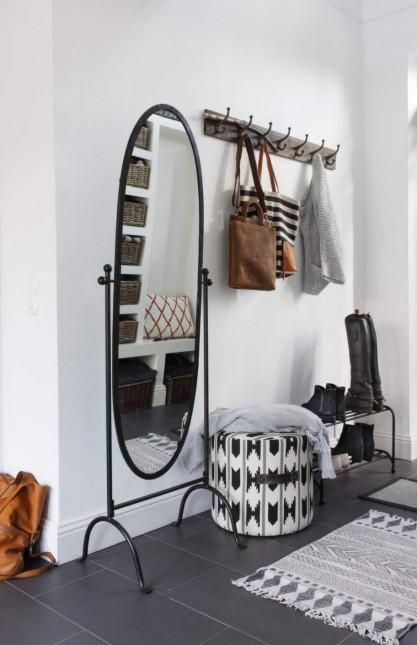 aranżacja korytarza w skandynawskim stylu,skandynawski styl w przedpokoju,skandynawska aranżacja z czarno-białymi meblami,skandynawski dywanik w etniczne wzory,jak urządzić korytarz w skandynawskim stylu,owalne lustro stojące,kute meble do przedpokoju,puf czarno-biały