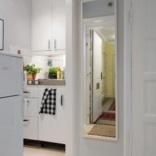 białe szafki kuchenne ze stalowym blatem w mini aneksie kuchennym w otwartym widoku z przedpokojem z prostokatnym bialym lustrem (25916)