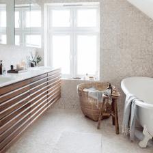 beżowo-biała mozaika na ścianie i posadzce włazience,bambusowy kosz na pranie,drewniane fronty umywalkowych szafek z białymi blatami (27884)