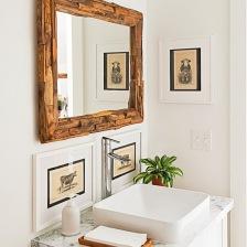 lustro z drewna,kamienny blat na szafce z umywalką,retro obrazki w białych ramkach na scianie w białej łazience (26165)