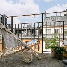 skandynawska letnia aranżacja małego balkonu z leżakiem,koszem z trawy morskiej i nastrojową latarenką (28456)