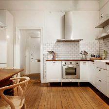 biała kuchnia w stylu skandynawskim z drewnianymi blatami, podłogą z desek i drewnianym stołem w brązowo-miodowym kolorze (27099)