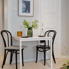 mały biały stolik z czarnymi giętymi z drewna krzesłami  w małej jadalni (25912)
