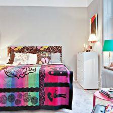 Kolorowe łóżko we wzory w sypialni z szarymi scianami (27855)
