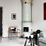 skandynawski bialy salon z ceramicznym piecem, szarą sofą,i nowoczesnym obraze, w brązach