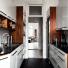 drewniane boki szafek i czarne blaty w malej białej kuchni
