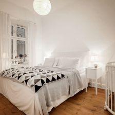 biało-szaro-czarne trójkaty na skandynawskiej narzucie w białej sypialni małżeńskiej z drewnianym dziecięcym łóżeczkiem (27100)