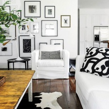 galeria biało-czarnej fotogreafi i grafik na białej ścianie w salonie z białymi fotelami i sofą i rustykalnym stołem z drewnianym blatem (26785)