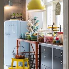betonowa ściana w kuchni z niebieską lodówką smeg,żółtą metalową lampą ,żółtym stołkiem ze schodkami i z turkusowo-żółtą porcelaną (27526)
