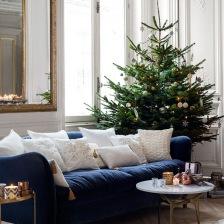 granatowa sofa z białymi poduszkami dekoracyjnymi, okragły stolik kawowy i świateczna choinka w salonie (27546)