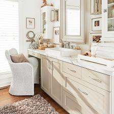 biała łazienka w tradycyjnej aranżacji z wiklinowym fotelem,drewnianym lustrem,drewnianą podłogą z desek i zabudową szafek z umywalką naszafkową (26167)